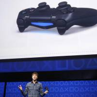 Taking control: A Sony official explains the controller features on the PlayStation 4 during an event in New York on Wednesday announcing the release of the new game console. | REUTERS/KYODO