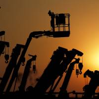 Looking up: Cranes and booms stand are silhouetted in January at a Tokyo equipment rental firm near a construction site. The government said Wednesday that industrial output picked up in February, upgrading its basic assessment of the economy for second straight month. | BLOOMBERG