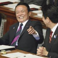 Seriousness aside: Finance Minister Taro Aso (left) has a light moment with Prime Minister Shinzo Abe during Thursday's Lower House plenary session. | AP