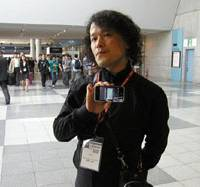 Augmented vision: Takahito Iguchi shows off an iPhone after speaking at the CEATEC technology conference in Chiba on Friday. Iguchi says his groundbreaking Sekai Camera application is only at the beginning of its evolution. | RICK MARTIN PHOTO