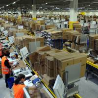 Automatons: Workers at Amazon logistic centers such as this one in in Bad Hersfeld, Germany, see little of the profits made by the online retailing giant. | AFP-JIJI