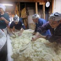 Something brewing: Myoho Asari (right), her father, Koichi (second from right), and son, Ryotoku (left), prepare steamed rice on Nov. 7 at their store, Kojima Honten, in Saiki, Oita Prefecture. | KYODO