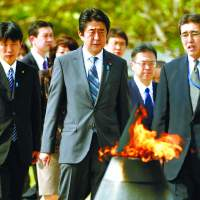 Collective respect: Prime Minister Shinzo Abe pays his respects to Okinawa's war dead Saturday at the Peace Memorial Park in Itoman, on the southernmost tip of Okinawa Island. | KYODO