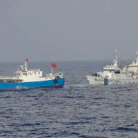 Closely shadowed: Coast guard cutters tail a Chinese fishing boat Saturday off Miyako Island in Okinawa Prefecture before officers boarded the vessel and arrested its captain on suspicion of illegally operating in Japan's exclusive economic zone. | JAPAN COAST GUARD/AP
