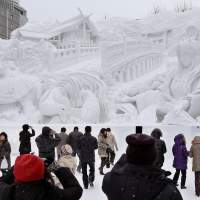 Frozen in time:  Visitors on Tuesday to the Sapporo Snow Festival view a gigantic sculpture based on an ancient Shinto myth at the start of the annual weeklong event. | KYODO