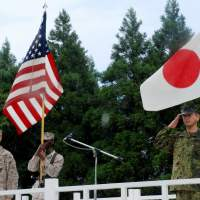 Military honors: Personnel from the Ground Self-Defense Force and U.S. Marine Corps salute during the opening ceremony for a joint military exercise last August at the Hijudai training center in Yufu, Oita Prefecture. | KYODO