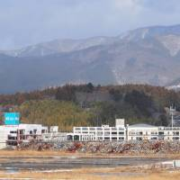 Going nowhere: The defunct Maiya department store (left) and Rikuzentakata's former City Hall next door are shown in isolation in December, serving as reminders of how slowly the city's restoration has proceeded since it was wiped out by the 2011 earthquake and tsunami.   COURTESY OF CITY OF RIKUZENTAKATA