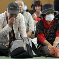 Just the beginning: Evacuees from the 20-km exclusion zone around Tokyo Electric Power Co.'s Fukushima No. 1 nuclear power station attend an event marking three months since the March 11 earthquake and tsunami, in Minamisoma, Fukushima Prefecture, on June 11, 2011. | BLOOMBERG
