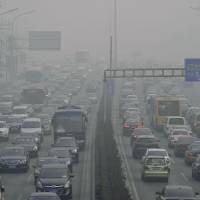 Industrial malaise: A Beijing highway is enveloped by thick smog last month as China's pollution worsens, and spreads. | KYODO