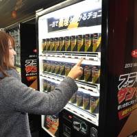 Love at first sight: A passenger gets a free can of Black Thunder chocolate bars Saturday from a vending machine set up for Valentine's Day at the Marunouchi Line's subway stop inside Shinjuku Station, Tokyo. | YOSHIAKI MIURA
