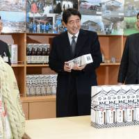 Raising spirits: Prime Minister Shinzo Abe (center) and postdisaster reconstruction minister Takumi Nemoto (right) visit a sake brewery in Ofunato, Iwate Prefecture, on Saturday. | POOL/KYODO