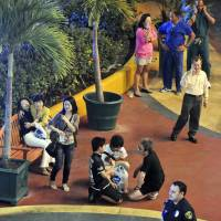 Grief-stricken: Witnesses comfort each other after a 21-year-old man allegedly drove a Toyota Yaris into a crowd of people in Tumon, Guam, on Tuesday before stabbing several of them. | AP