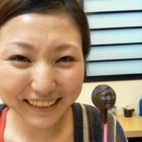 The look of love:  Tokyo office worker Mariya Kawae shows a chocolate molded from her face during a workshop on Feb. 9 in which the participants were scanned and the data sent to a 3-D printer. | KYODO