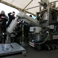 Blaster-master: A Toshiba Corp. prototype remote-controlled decontamination robot blasts dry ice to show how it would peel off radioactive materials, and then later vacuum them up, at the firm's Yokohama complex Friday. | KAZUAKI NAGATA