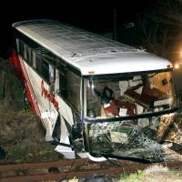 Train wreck: A tour bus lies across the JR Kyudai Line in Kokonoe, Oita Prefecture, on Sunday after careering onto the track. | KYODO