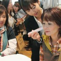 Top customers: A woman in her 40s tries out a skin care product during an event in Tokyo's Shibuya Ward recently. | KYODO