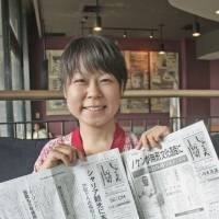 No regrets: Reporter Miki Hotta, 26, holds up the Daily Jakarta Shimbun in Jakarta on Jan. 25. | KYODO