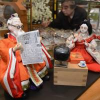 All dolled up: A pair of Hina dolls wearing glasses and relaxing in front of a television are displayed in the front of a Gujo, Gifu Prefecture, eyewear shop earlier this month. | KYODO