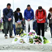 Still Mourning their lossRelatives of Japanese who died when the CTV Building in Christchurch, New Zealand, collapsed in an earthquake in 2011 pray Friday on the anniversary of the tragedy at the site where the structure once stood. | KYODO