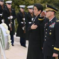 Respect: Prime Minister Shinzo Abe prays after laying a wreath at the Tomb of the Unknowns at Arlington National Cemetery in Virginia on Friday during his trip to the United States. | KYODO