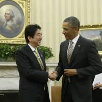 Shake it: Prime Minister Shinzo Abe and President Barack Obama chat after their meeting Friday in the Oval Office in Washington. | AP