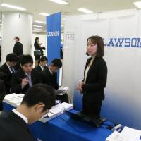Mining a new resource: An official at convenience store chain Lawson Inc. draws a big crowd during a recruitment forum for international students studying in Japan on Feb. 19 in Tokyo's Ikebukuro district. | KAZUAKI NAGATA