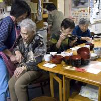 Aiding mobility: Kimi Ouchi, 85, is helped to her feet by an employee as two other seniors eat dinner at a privately run home for the elderly in Yubari, Hokkaido, in March 2007. | BLOOMBERG