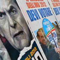 Mixed message: Electoral placards showing Democratic Party leader Pier Luigi Bersani (left) and rightwing rival Silvio Berlusconi are plastered to a wall in Rome on Monday. | AFP-JIJI