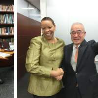 South African Ambassador Mohau Pheko celebrates with  Toshio Akiniwa (right), who was awarded the Order of the Companions of O.R.  Tambo, at a commemorative event at the embassy in Tokyo on Jan. 28. During the event, Akiniwa shows a photo of the award ceremony held in Pretoria last October.  | EMBASSY OF SOUTH AFRICA