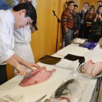 Beyong lox: A representative of Hiroshima-based seafood firm Rumi Japan slices a yellowtail Tuesday at a tasting event for food industry officials at the official residence of the Japanese ambassador to Israel.  | KYODO PHOTO