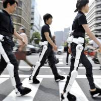 Power assist: Cyberdyne Inc. employees wearing Hybrid Assistive Limb, or HAL, robotic suits are seen in 2009. The gear received safety certification Wednesday by a quality assurance organization.   | AFP-JIJI