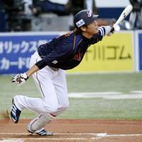 Strike while it's hot: Japan's Hayato Sakamoto hits a sacrifice fly against Australia on Sunday. Japan won 10-3. | KYODO