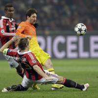 Marked man: Barcelona's Lionel Messi is tackled by AC Milan's Massimo Ambrosini (front) in their Champions League match at San Siro Stadium on Wednesday night. Milan won 2-0. | AP