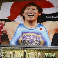 Endangered species: A man runs past a billboard featuring three-time Olympic gold medal-winning wrestler Saori  Yoshida in  Tokyo on  Tuesday. The IOC's executive board voted the same day to cut wrestling from the 2020 Games. | KYODO