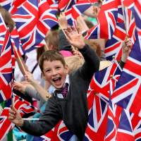 Jubilation: Children cheer during the Olympic Torch Relay on June 18. London won the right to host the games largely on its promise to put in place policies to boost sports participation, but the government is slashing funding for sports at schools. | AP