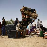 From Timbuktu to here:  Fleeing Malians load a pickup truck with goods and furniture on Sunday after crossing the Niger River at the port of Korioume, south of Timbuktu. Defense officials said Sunday that the first supply convoy of food, fuel and parts to eastern Mali was heading across the country. | AP