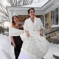 White wedding: Kathryn Jussaume steps into snowshoes outside her parents' home as her sister and maid of honor, Adrianne, laughs ahead of her wedding Saturday in Lowell, Massachusetts. | AP