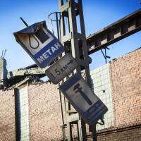 And the walls came tumbling down: A damaged street sign leans outside a zinc plant in Chelyabinsk after a shock wave from a meteor crash crumbled parts of the wall Friday. | AFP-JIJI
