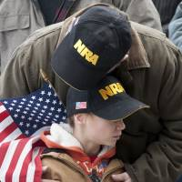 Hereditary right: A gun-rights supporter hugs his son during a rally at the Capitol in Hartford, Connecticut, on Jan. 19.  The rally, dubbed, 'Guns Across America,' was one of many held at state capitol buildings nationwide to raise concerns about possible new legislation that could affect gun owners' rights in the wake of the Dec. 14 school shooting at Sandy Hook Elementary School in Newtown, Connecticut. | AP