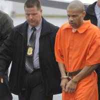 Serial rapist: Convicted rapist Aaron Thomas arrives in handcuffs at an airport in Manassas, Virginia, on Nov. 29, 2011. | THE WASHINGTON POST