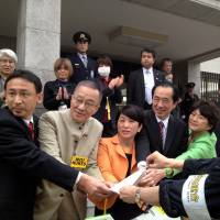 An antinuclear protester hands a petition to a group of Diet lawmakers including former Prime Minister Naoto Kan and Social Democratic Party leader Mizuho Fukushima Sunday in Tokyo. | AYAKO MIE