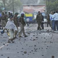 Another assault: A woman walks past a group of policemen standing guard on a road strewn with glass and stones in New Delhi on Friday following a protest over the rape of a 7-year-old girl at a school. | AP