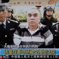 Final steps: This frame grab from China's state-run CCTV-9 on Friday shows convicted murderer Yi Lai being led from a prison cell to the site of his execution in Yunnan Province.   AFP-JIJI