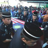 Another casualty: Malaysian police officers carry a coffin containing a dead police commando killed during a standoff with Sulu gunmen in Tanduo village, near Lahad Datu, shortly after it arrived at Subang Royal Malaysian Air Force Base in Kuala Lumpur on Saturday. | AFP-JIJI