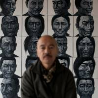 Freedom of expression: Liu Yi poses with his black-and-white oil paintings of Tibetan self-immolators at his Spartan studio on the outskirts of Beijing on Feb. 21. | AFP-JIJI