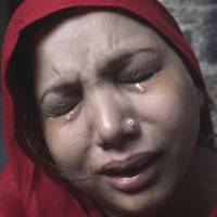 Disturbing sight: A Pakistani Christian woman weeps following a visit to her home after it was damaged by an angry Muslim mob in Lahore on Sunday. | AP