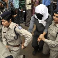 Safety issues: A Swiss woman who police say was gang-raped while touring central India by bicycle with her husband is led to a hospital in Gwalior for a medical examination Saturday.   AP