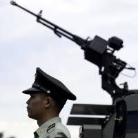 Going global: A People's Liberation Army soldier stands next to an armored personnel carrier during the Barracks Open Days at the PLA's Hong Kong garrison in May 2011. | BLOOMBERG