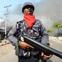 On the front line: A policeman stands guard in Meikhtila, Myanmar, on Friday. | AFP-JIJI