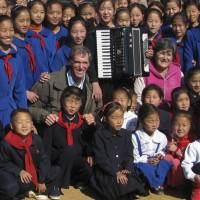 Kith and Kim?: U.S. citizen Christopher Carpenter (center left) and French national Catherine Bertrand (center right) pose with students at a new school in the North Korean village of Yonhung-ri in South Hwanghae Province in October 2011. | AFP-JIJI